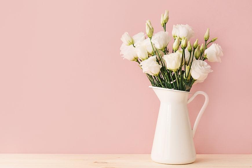 Róże i goździki w wazonie wyglądającym jak konewka
